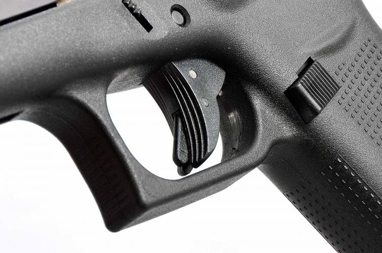 Particolare del grilletto zigrinato dotato della peculiare sicura a leva