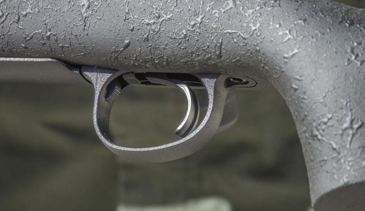Di fronte al grilletto, all'interno della guardia, è visibile il pulsante di apertura dello sportello del caricatore