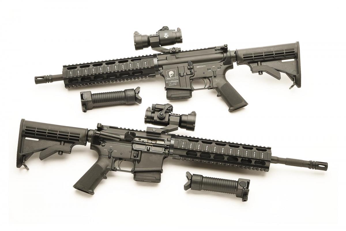 """Sopra, lo SDM M4 Commando con canna da 12"""". Sotto, lo SDB M4 Carbine con canna da 14.5"""". Entrambi i modelli sono venduti in kit con ottica a punto rosso e impugnatura frontale con bipiede incorporato."""