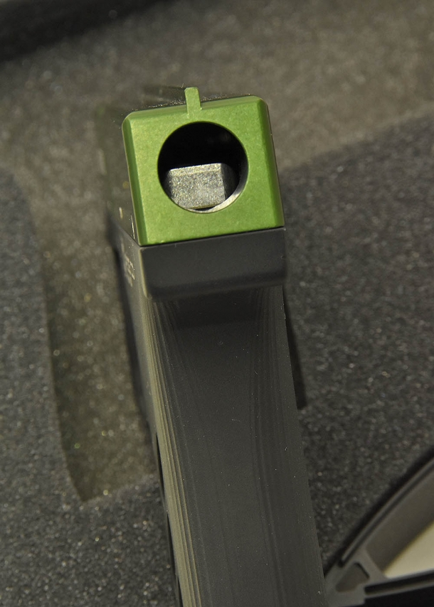 A close-up of the lever activated by the trigger that squeezes the canister within the device to release the spray