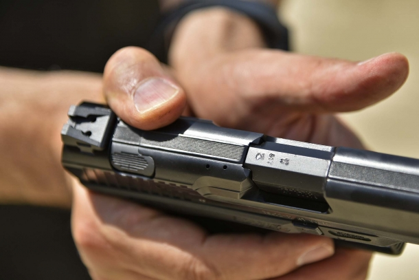 Il pulsante ambidestro di disarmo del percussore della Canik TP9 v2 azionato con il pollice della mano forte