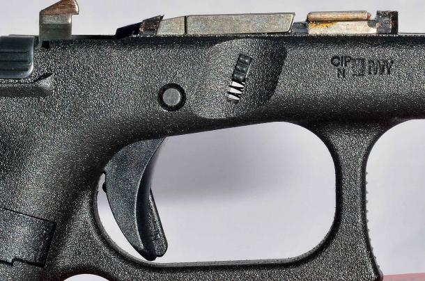 Si intravede nella fessura di scorrimento la molla a spirale che comanda il pulsante di smontaggio della Glock G19 Gen 5 calibro 9mm