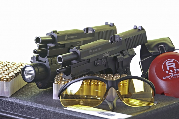 Left to right: the S.D.M. XM9 Operator variant, factory-issued with a tactical flashlight, and the baseline S.D.M. XM9 Tactical model