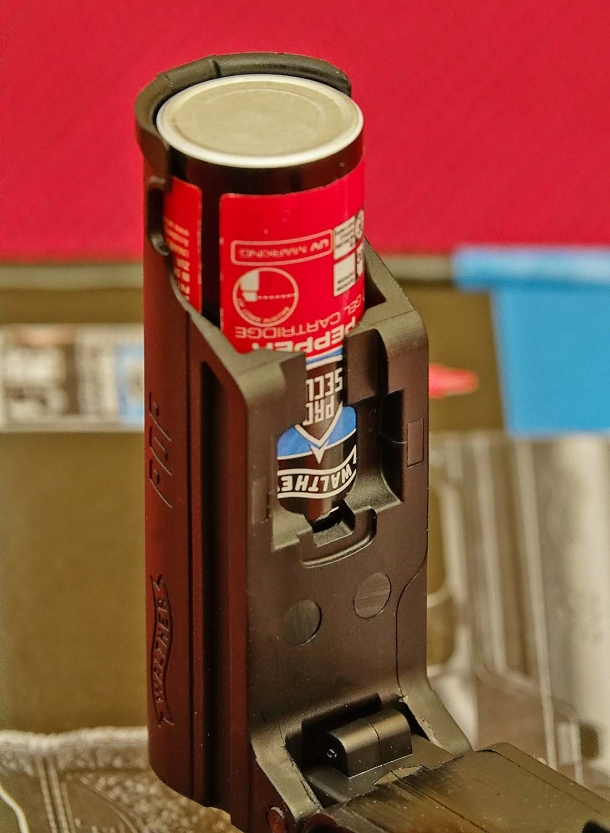 A slot on the side of the Walther PDP allows the user to peek through and recognize the type of pepper cartridge inserted by the color of the label: black for pepper spray, red for pepper gel, white for training water cartridge