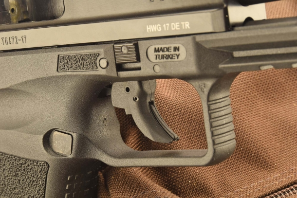 A close-up of the Canik TP9 SF trigger and its safety