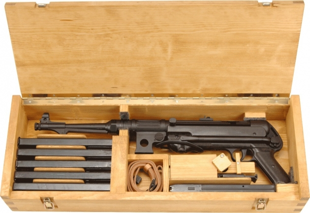 The BD 38's wooden box includes a sling, various magazines, and several other accessories