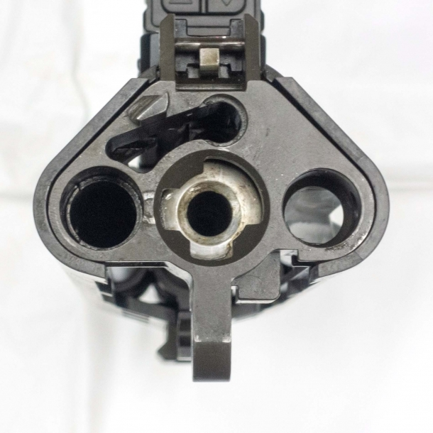 Rear view of the upper receiver. On top is the seat of the contact point between the bolt group and the ambidextrous charging handle; on the bottom, from left to right, are respectively the gas piston seat; the chamber; and the forward chute for spent cases