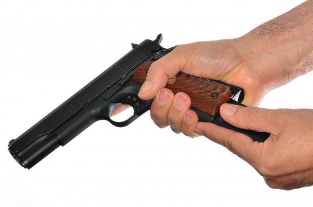 l'accertamento inizia estraendo il serbatoio dal fusto della pistola. in questa fase non si deve mani passare l'arma da una mano all'altra. notare l'indice posto davanti la costolatura del serbatoio