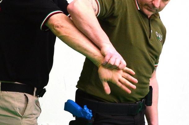2 - una forte pressione applicata sul lato interno della mano e successiva rotazione,  costringe l'avversario a lasciare la presa dall'arma