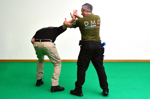 4 - si applica una pressione sull'articolazione del braccio che si piega, costringendo l'avversario a curvare contemporaneamente la schiena