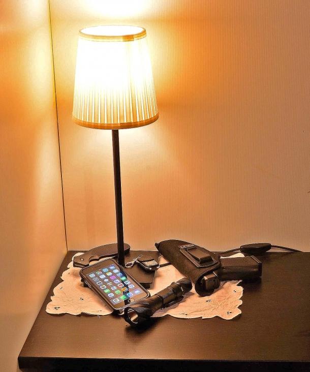 un comodino attrezzato per la notte, pistola, torcia tattica, una lama, cellulare, telecomando antifurto