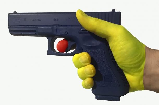 L'illustrazione evidenzia le due forze che occorre controllare durante l'azione del tiro. L'indice (in rosso) aumenta progressivamente la pressione. La mano (in giallo) che avvolge l'impugnatura esercita una pressione senza variazioni d'intensità