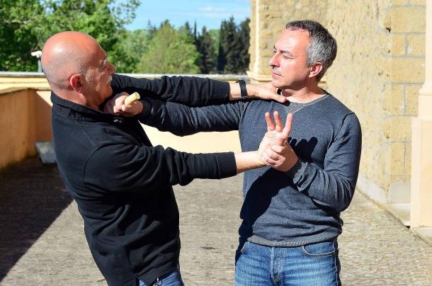 una leva articolare con torsione della mano supportata da pressione  esercitata con il palm stick alla base del collo